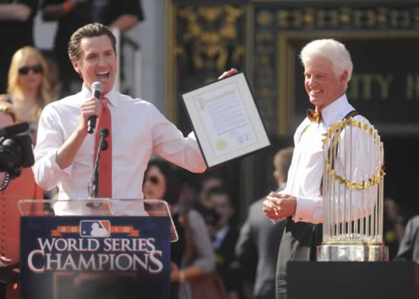 San Francisco Mayor Gavin Newsom, left, reads a proclamation as San Francisco Giants owner Bill Neukom, right, looks on during the Giants' World Series victory celebration at Civic Center Plaza in San Francisco, Wednesday, Nov. 3, 2010.(AP Photo/Noah Berger)