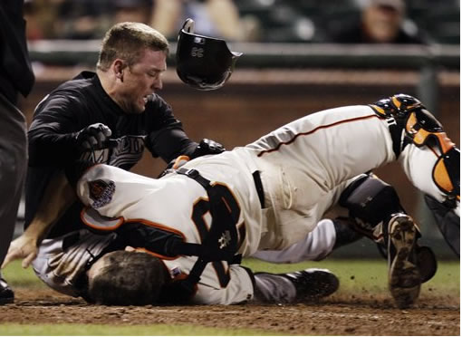 Florida Marlins' Scott Cousins, top, collides with San Francisco Giants catcher Buster Posey (28) on a fly ball from Emilio Bonifacio during the 12th inning of a baseball game in San Francisco, Wednesday, May 25, 2011. Cousins was safe for the go ahead run and Florida won 7-6. (AP Photo/Marcio Jose Sanchez)