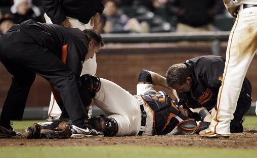 San Francisco Giants catcher Buster Posey (28) is tended by trainers after a collision with Florida Marlins' Scott Cousins on a fly ball from Emilio Bonifacio during the 12th inning of a baseball game in San Francisco, Wednesday, May 25, 2011. Cousins was safe for the go ahead run and Florida won 7-6. (AP Photo/Marcio Jose Sanchez)