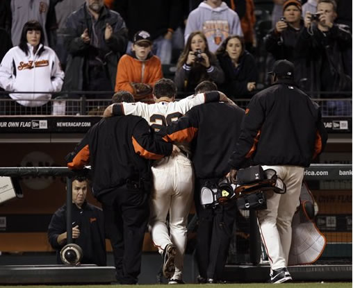 San Francisco Giants catcher Buster Posey (28) is carried off the field after a collision with Florida Marlins' Scott Cousins during the 12th inning of a baseball game in San Francisco, Wednesday, May 25, 2011. Cousins scored the go-ahead run on the play as Florida won 7-6. (AP Photo/Marcio Jose Sanchez)