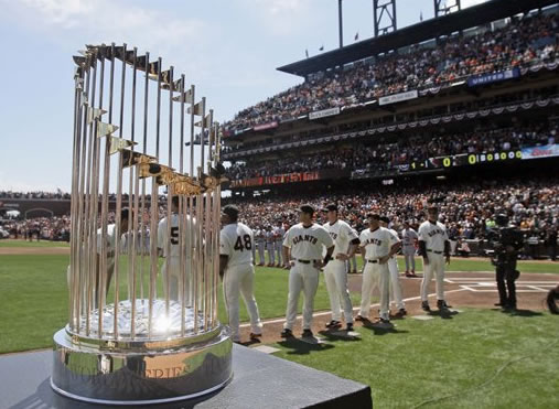 The San Francisco Giants look on next to their World Series trophy as they prepare to face the St. Louis Cardinals in their home-opening baseball game in San Francisco, Friday, April 8, 2011. (AP Photo/fPool, Marcio Jose Sanchez)