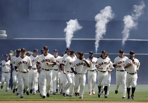 The San Francisco Giants run together as they are introduced before the start of their home-opening baseball game against the St. Louis Cardinals in San Francisco, Friday, April 8, 2011. (AP Photo/Marcio Jose Sanchez)