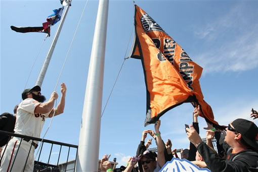 San Francisco Giants relief pitcher Brian Wilson raises the team's World Series championship flag before their home-opening baseball game against the St. Louis Cardinals in San Francisco, Friday, April 8, 2011. (AP Photo/Getty Images, Justin Sullivan, Pool)