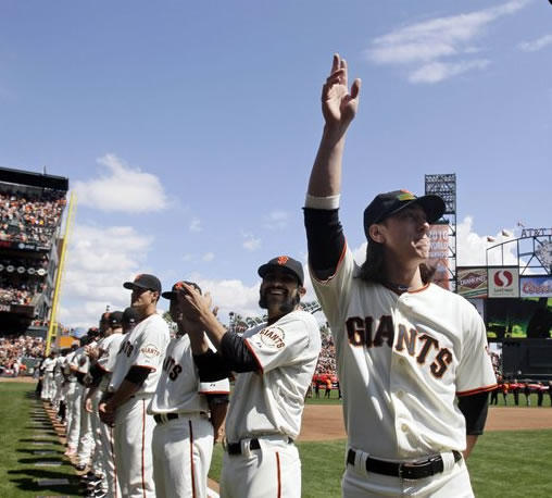 San Francisco Giants' Tim Lincecum, right, acknowledges fans next to teammate Sergio Romo before their home-opening baseball game against the St. Louis Cardinals in San Francisco, Friday, April 8, 2011. (AP Photo/Marcio Jose Sanchez)