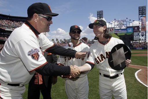 San Francisco Giants manager Bruce Bochy, left, shakes hands with starting pitcher Tim Lincecum as center fielder Cody Ross, center, looks on after both players received post season awards following their 2010 World Series campaign before the start of a baseball game against the St. Louis Cardinals in San Francisco, Friday, April 8, 2011. (AP Photo/Marcio Jose Sanchez)