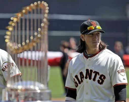 San Francisco Giants' Tim Lincecum looks on next to the team's World Series Trophy during player introductions before a baseball game against the St. Louis Cardinals in San Francisco, Friday, April 8, 2011. (AP Photo/Marcio Jose Sanchez, Pool)