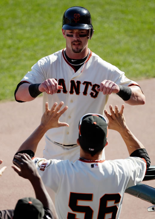San Francisco Giants' Aaron Rowand is congratulated by Andres Torres (56) after Rowand scored on an error by Philadelphia Phillies' Chase Utley during the fifth inning of Game 3 of baseball's National League Championship Series Tuesday, Oct. 19, 2010, in San Francisco. (AP Photo/Ben Margot)