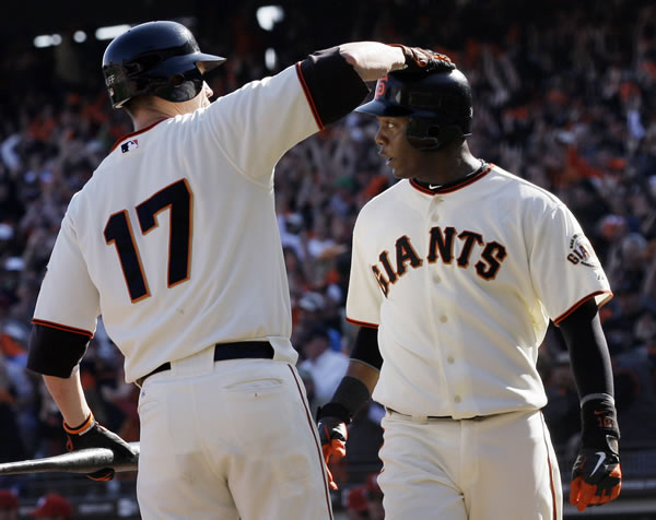 San Francisco Giants' Edgar Renteria is congratulated by Aubrey Huff (17) after scoring from second on a hit by Cody Ross during the fourth inning of Game 3 of baseball's National League Championship Series against the Philadelphia Phillies Tuesday, Oct. 19, 2010, in San Francisco. (AP Photo/Jeff Chiu)