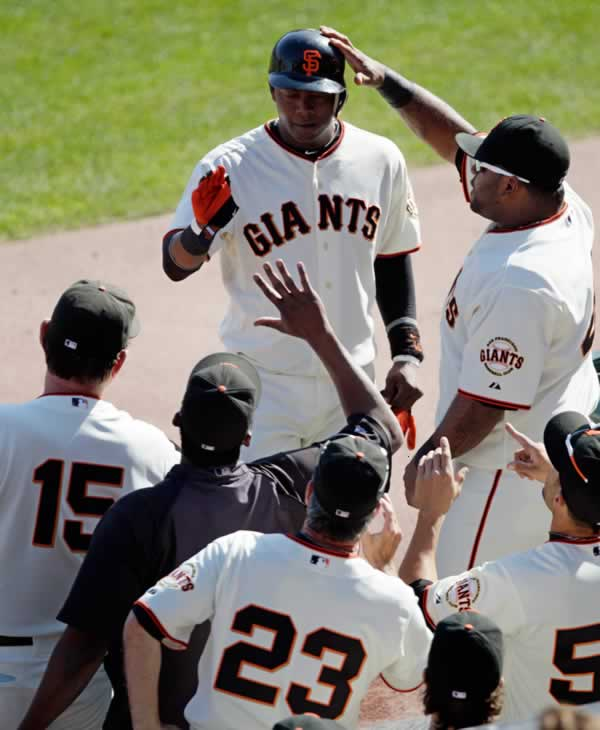 San Francisco Giants' Edgar Renteria is congratulated after scoring from second on a hit by Cody Ross during the fourth inning of Game 3 of baseball's National League Championship Series against the Philadelphia Phillies Tuesday, Oct. 19, 2010, in San Francisco. (AP Photo/Ben Margot)