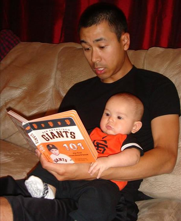 This is a picture of my son Tyler wearing a giants onesie while sitting with my husband reading a giants book. We raise kids right in this house!   (Photo submitted by Julie Francisco via uReport)