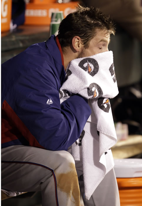Texas Rangers' Cliff Lee wipes his face in the dugout after being pulled during the fifth inning of Game 1 of baseball's World Series against the San Francisco Giants Wednesday, Oct. 27, 2010, in San Francisco. (AP Photo/David J. Phillip)