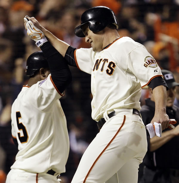 San Francisco Giants' Pat Burrell celebrates with Juan Uribe after scoring on an RBI single by Aubrey Huff during the sixth inning of Game 1 of baseball's World Series against the Texas Rangers Wednesday, Oct. 27, 2010, in San Francisco. (AP Photo/David J. Phillip)