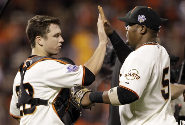 San Francisco Giants' Juan Uribe (5) and Buster Posey (28) celebrate after Game 1 of baseball's World Series against the Texas Rangers Wednesday, Oct. 27, 2010, in San Francisco. The Giants won 11-7 to take a 1-0 lead in the series. (AP Photo/David J. Phillip)
