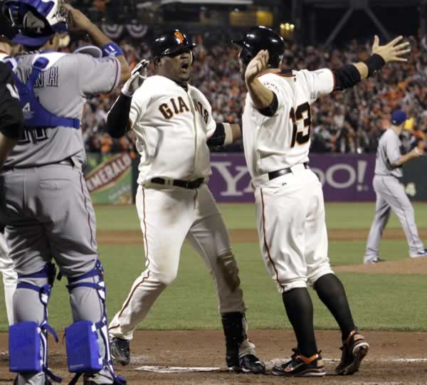 San Francisco Giants' Juan Uribe, right, is congratulated at home by Cody Ross (13) after Uribe hit a three-run home run during the fifth inning of Game 1 of baseball's World Series against the Texas Rangers Wednesday, Oct. 27, 2010, in San Francisco. (AP Photo/David J. Phillip)