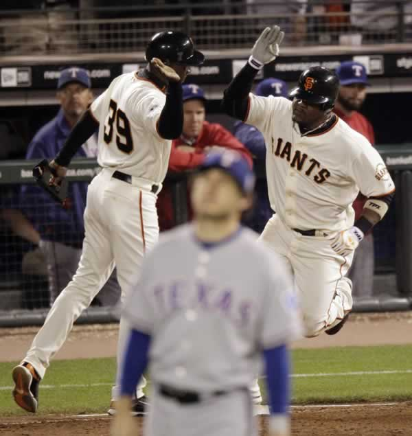 San Francisco Giants first base coach Roberto Kelly (39) congratulates Juan Uribe after Uribe hit a three-run home run during the fifth inning of Game 1 of baseball's World Series against the Texas Rangers Wednesday, Oct. 27, 2010, in San Francisco. (AP Photo/Eric Gay)