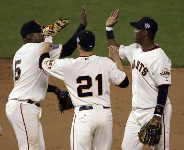 San Francisco Giants' Juan Uribe (5), Freddy Sanchez (21) and Edgar Renteria celebrate after Game 2 of baseball's World Series against the Texas Rangers Thursday, Oct. 28, 2010, in San Francisco. The Giants won 9-0 to take a 2-0 lead in the series. (AP Photo/Eric Risberg)