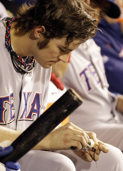 Texas Rangers' C.J. Wilson works on his inger after leaving the game during the seventh inning of Game 2 of baseball's World Series against the San Francisco Giants Thursday, Oct. 28, 2010, in San Francisco. (AP Photo/David J. Phillip)