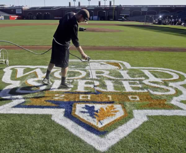 Workers paint the field at AT&T Park before practice for Game 1 of baseball's World Series between the San Francisco Giants and the Texas Rangers Tuesday, Oct. 26, 2010, in San Francisco. (AP Photo/Jeff Chiu)