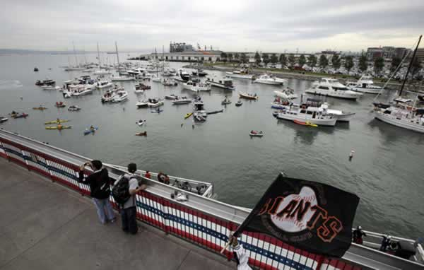 Fans watch boats line up in McCovey Cove before Game 1 of baseball's World Series between the San Francisco Giants and the Texas Rangers Wednesday, Oct. 27, 2010, in San Francisco. (AP Photo/Eric Risberg)