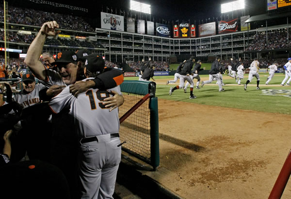 San Francisco Giants manager Bruce Bochy, left, celebrates in the dugout after Game 5 of baseball's World Series against the Texas Rangers Monday, Nov. 1, 2010, in Arlington, Texas. The Giants won 3-1 to capture the World Series. (AP Photo/Matt Slocum)
