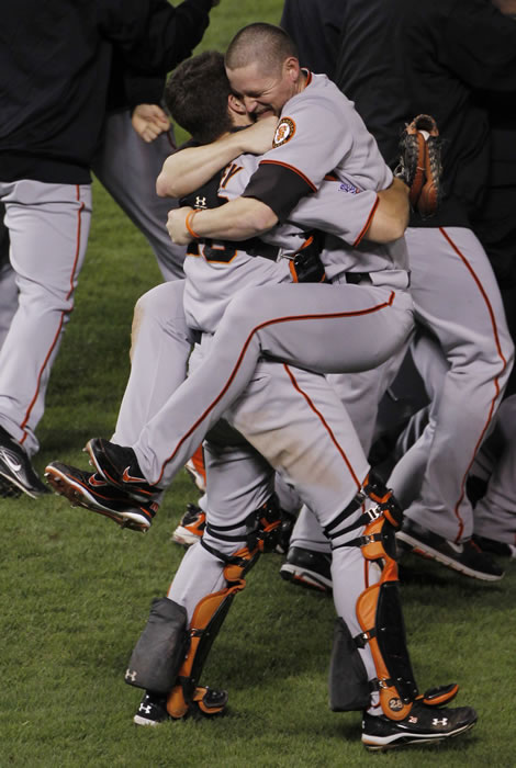 San Francisco Giants Aubrey Huff hugs with Buster Posey, left, after winning the World Series in Game 5 of baseball's World Series against the Texas Rangers Monday, Nov. 1, 2010, in Arlington, Texas. The Giants won 3-1 to capture the series. (AP Photo/David J. Phillip)