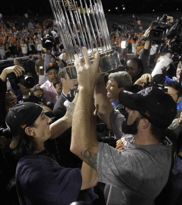 San Francisco Giants' Tim Lincecum hands over the World Series trophy to Brian Wilson after winning baseball's World Series against the Texas Rangers Monday, Nov. 1, 2010, in Arlington, Texas. The Giants won 3-1 to capture the World Series. (AP Photo/David J. Phillip)
