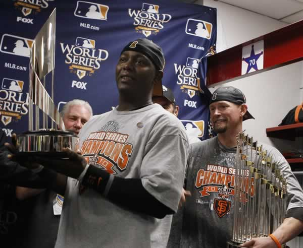San Francisco Giants Edgar Renteria holds the Most Valuable Player trophy after Game 5 of baseball's World Series against the Texas Rangers Monday, Nov. 1, 2010, in Arlington, Texas. Aubrey Huff holds the World Series trophy at right. The Giants won 3-1 to capture the World Series. (AP Photo/Matt Slocum)