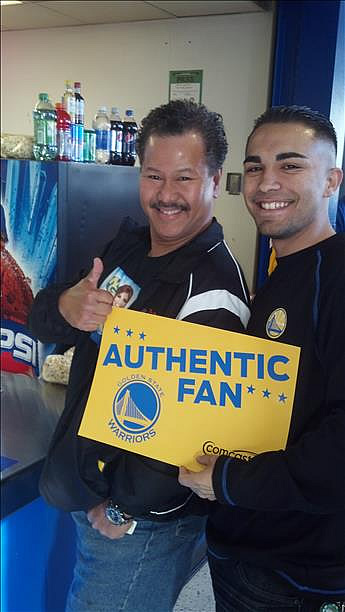 Two Warriors fans pose for a photo while they hold a sign