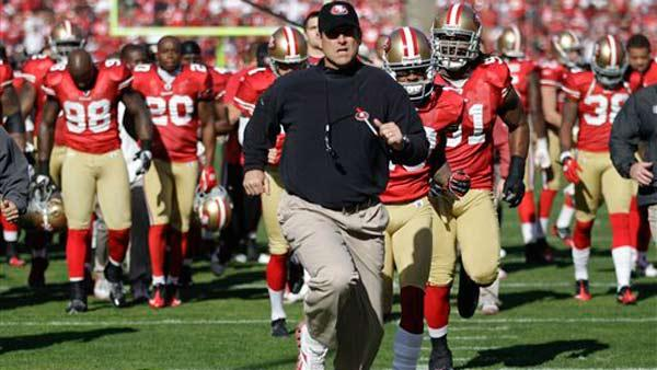 San Francisco 49ers coach Jim Harbaugh runs off the field with his team before playing the New Orleans Saints in an NFL divisional playoff football game Saturday, Jan. 14, 2012, in San Francisco. (AP Photo/Paul Sakuma)
