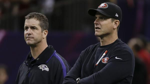 San Francisco 49ers head coach Jim Harbaugh, right, and Baltimore Ravens head coach John Harbaugh look on during practice before the NFL Super Bowl XLVII.