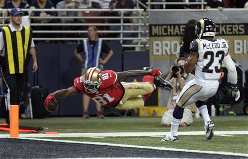 San Francisco 49ers wide receiver Anquan Boldin, left, dives into the end zone with a 20-yard touchdown reception as St. Louis Rams safety Rodney McLeod watches during the second quarter of an NFL football game Thursday, Sept. 26, 2013, in St. Louis. <span class=meta>(AP Photo&#47;Tom Gannam)</span>