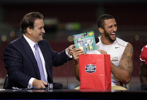 San Francisco 49ers quarterback Colin Kaepernick, right, laughs about a gift given to him by the NFL Network crew including Steve Mariucci, left, during the fourth quarter of an NFL football game Thursday, Sept. 26, 2013, in St. Louis. <span class=meta>(AP Photo&#47;Charlie Riedel)</span>