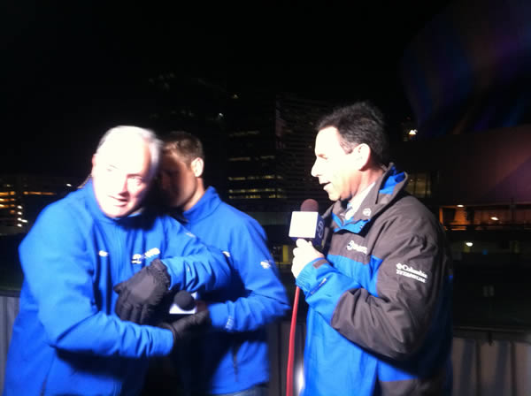 Mike Shumann does a microphone handoff with Colin Resch during the newscast.