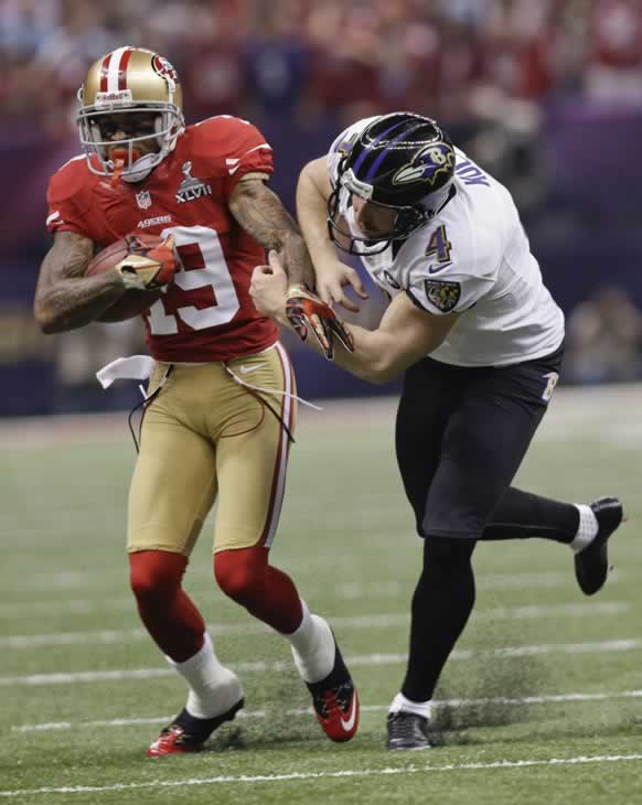San Francisco 49ers wide receiver Ted Ginn Jr., (19) is pushed out of bounds by Baltimore Ravens punter Sam Koch (4) on his way to a first down in the third quarter of the NFL Super Bowl XLVII football game Sunday, Feb. 3, 2013, in New Orleans. (AP Photo/Dave Martin)