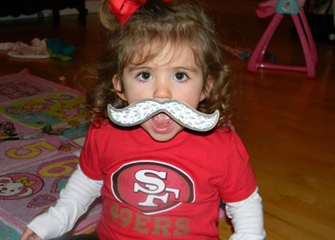 "<div class=""meta ""><span class=""caption-text "">Isabelle C., 20 months from San Jose, with her Sourdough Sam mustache showing her Niner pride! (Photo submitted via uReport)</span></div>"