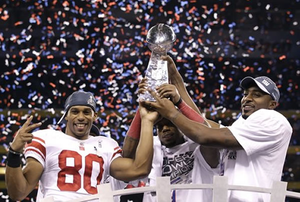 New York Giants players including wide receiver Victor Cruz, left, and wide receiver Hakeem Nicks, right, celebrate their team's 21-17 win over the New England Patriots in the NFL Super Bowl XLVI football game, Sunday, Feb. 5, 2012, in Indianapolis. (AP Photo/David J. Phillip)