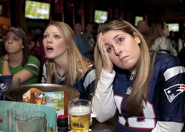 Kerry Harrington, center, and Sara Laporte, right, both of Boston, react while watching the NFL football Super Bowl game between the New York Giants and the New England Patriots on television at a bar in Boston, Sunday, Feb. 5, 2012. The Giants won 21-17. (AP Photo/Michael Dwyer)