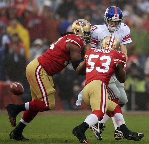 New York Giants quarterback Eli Manning fumbles as he is hit by San Francisco 49ers' Ray McDonald (91) and NaVorro Bowman (53) during the first half of the NFC Championship NFL football game Sunday, Jan. 22, 2012, in San Francisco. (AP Photo/Marcio Jose Sanchez)