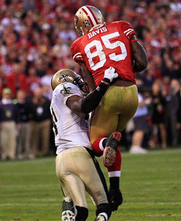 San Francisco 49ers tight end Vernon Davis (85) scores on a 14-yard touchdown pass from quarterback Alex Smith over New Orleans Saints strong safety Roman Harper (41) during the fourth quarter of an NFL divisional playoff football game Saturday, Jan. 14, 2012, in San Francisco. (AP Photo/Marcio Jose Sanchez)