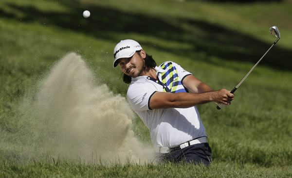 Jason Day, of Australia, hits out of a bunker on...