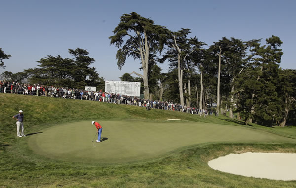 Dustin Johnson watches as Rickie Fowler putts on the 18th hole during the first round of the U.S. Open Championship golf tournament Thursday, June 14, 2012, at The Olympic Club in San Francisco. (AP Photo/Charlie Riedel)