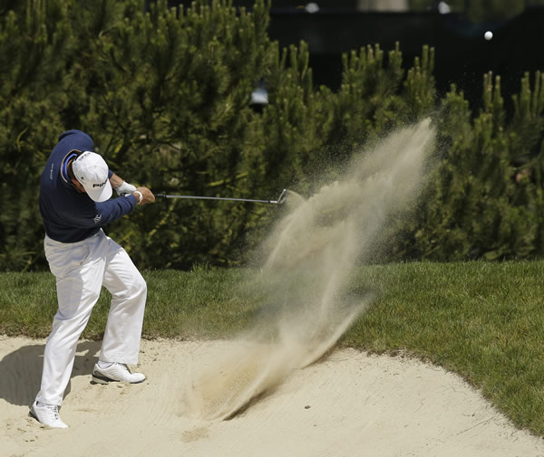 Lee Westwood, of England, hits out of a bunker...