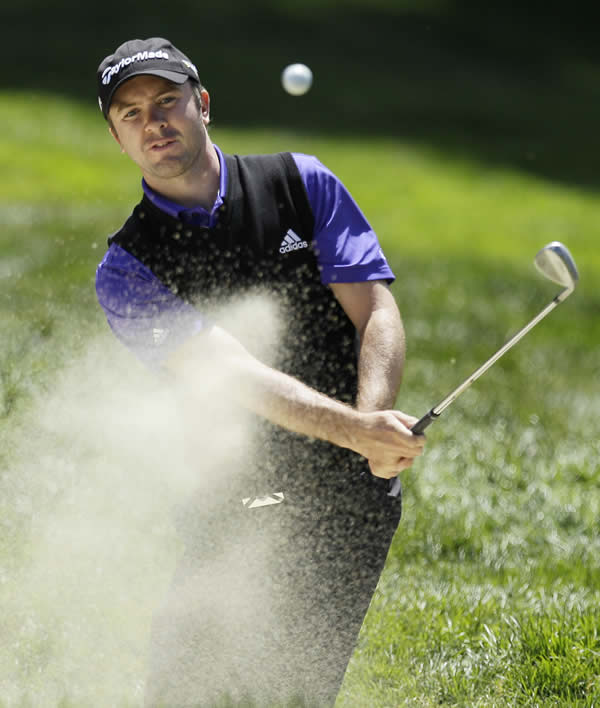 Martin Laird, of Scotland, hits out of a bunker...