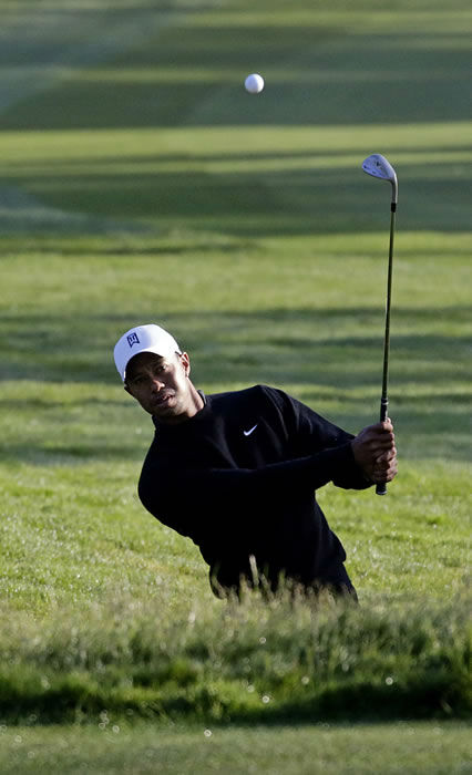 Tiger Woods hits out of some rough during a practice round for the U.S. Open Championship golf tournament Monday, June 11, 2012, in San Francisco. (AP Photo/Morry Gash)