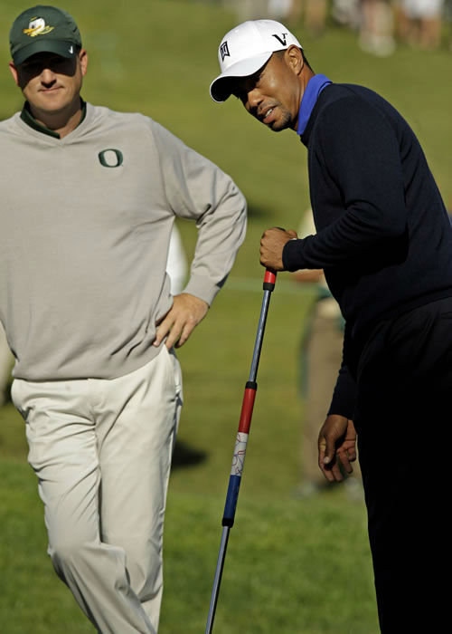 Casey Martin, left, watches as Tiger Woods uses Martin's putter on the fifth hole during a practice round for the U.S. Open Championship golf tournament Tuesday, June 12, 2012, at The Olympic Club in San Francisco. (AP Photo/Charlie Riedel)