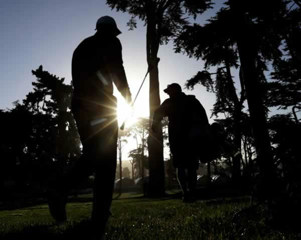 Tiger Woods, left, and his his caddie Joe LaCava make their way to the 10th tee during a practice round for the U.S. Open Championship golf tournament Monday, June 11, 2012, in San Francisco. (AP Photo/Morry Gash)