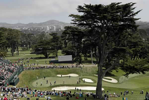 Golfers putt on the 18th green during a practice round for the U.S. Open Championship golf tournament Tuesday, June 12, 2012, at The Olympic Club in San Francisco. (AP Photo/Charlie Riedel)