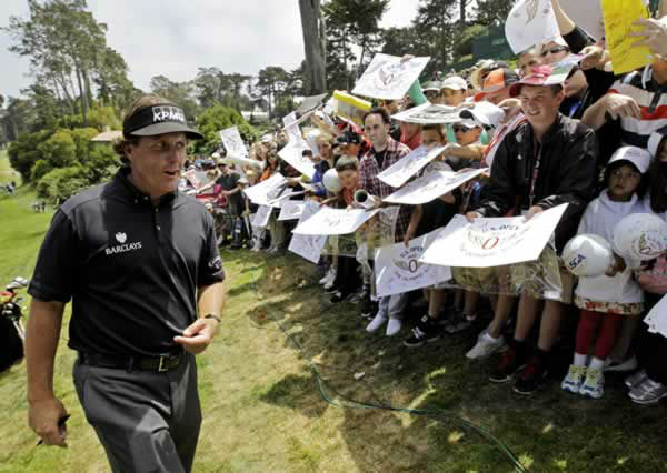 Phil Mickelson signs autographs after a practice round for the U.S. Open Championship golf tournament Tuesday, June 12, 2012, at The Olympic Club in San Francisco. (AP Photo/Eric Gay)