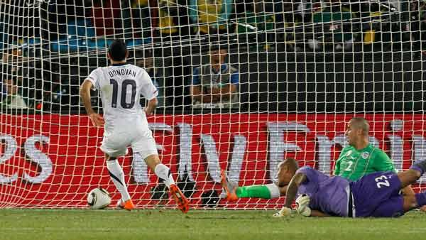 United States' Landon Donovan, left, scores a goal past Algeria goalkeeper Rais M'Bolhi, front right, and Algeria's Madjid Bougherra, back right, during the World Cup group C soccer match between the United States and Algeria.
