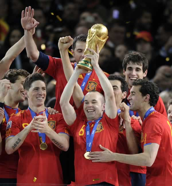 Spain's Andres Iniesta, center, holds up the World Cup trophy as he celebrates with fellow team members following the World Cup final soccer match between the Netherlands and Spain at Soccer City in Johannesburg, South Africa, Sunday, July 11, 2010. (AP Photo/Martin Meissner)